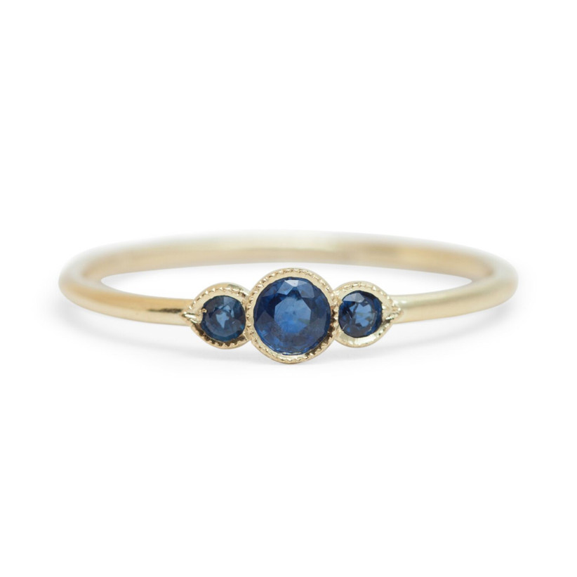 Minimalist three-stone sapphire engagement ring with yellow gold band