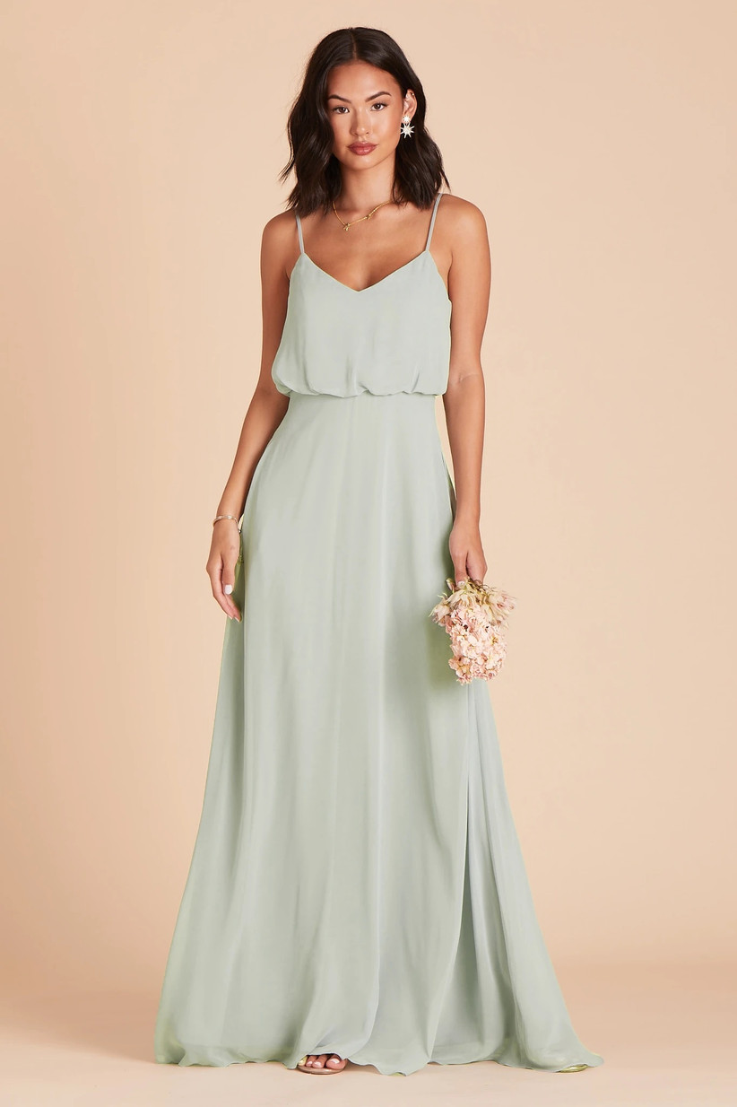 Model wearing minimalist pastel green bridesmaid dress with blouson bodice and flowy chiffon skirt