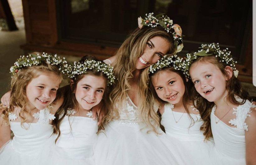 bride hugs her four flower girls who are wearing greenery and baby's breath crowns