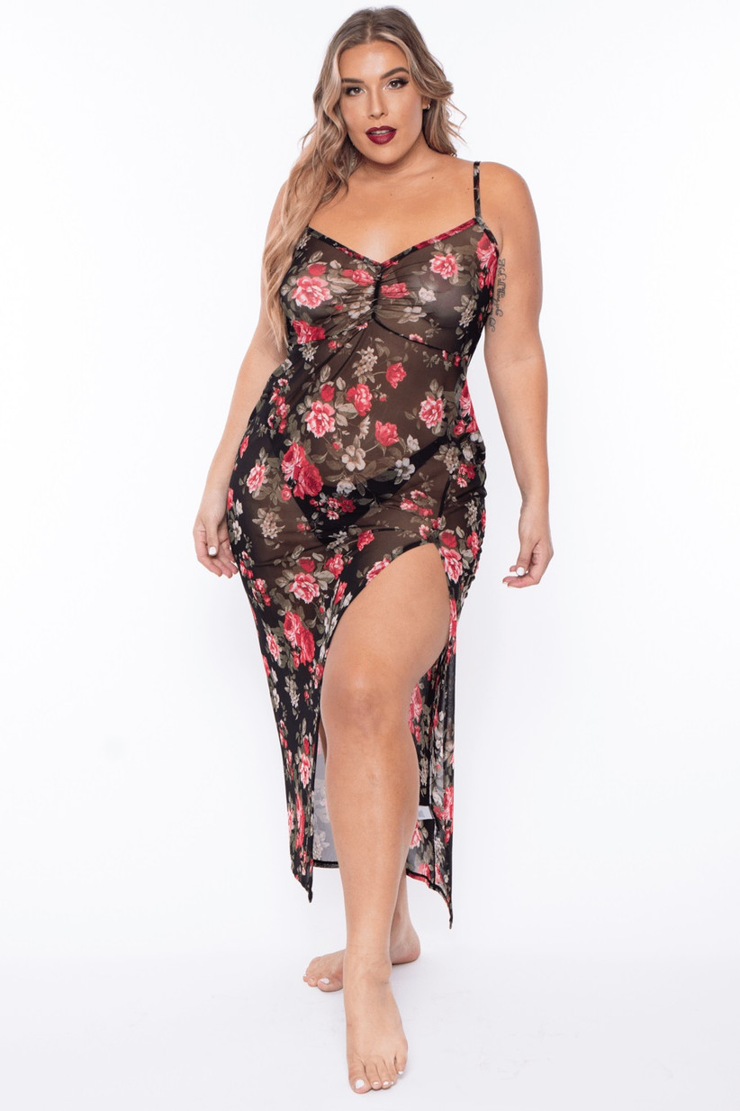 Model wearing long black sheer slip with leg slit and rose pattern with black thong underneath