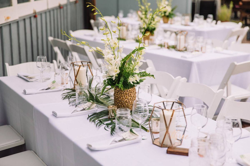 simple beach wedding centerpiece white orchids with tropical greenery and candles in gold geometric vases