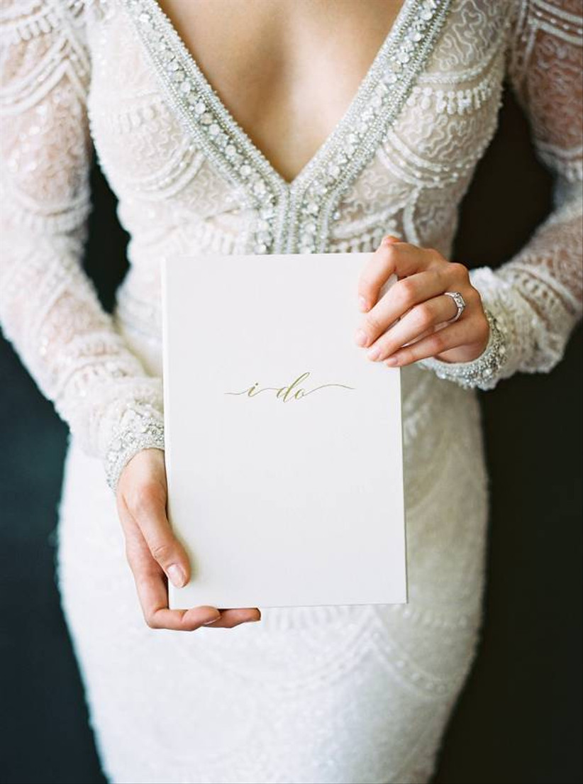 """bride holds a wedding journal embossed with """"i do"""" in gold calligraphy"""