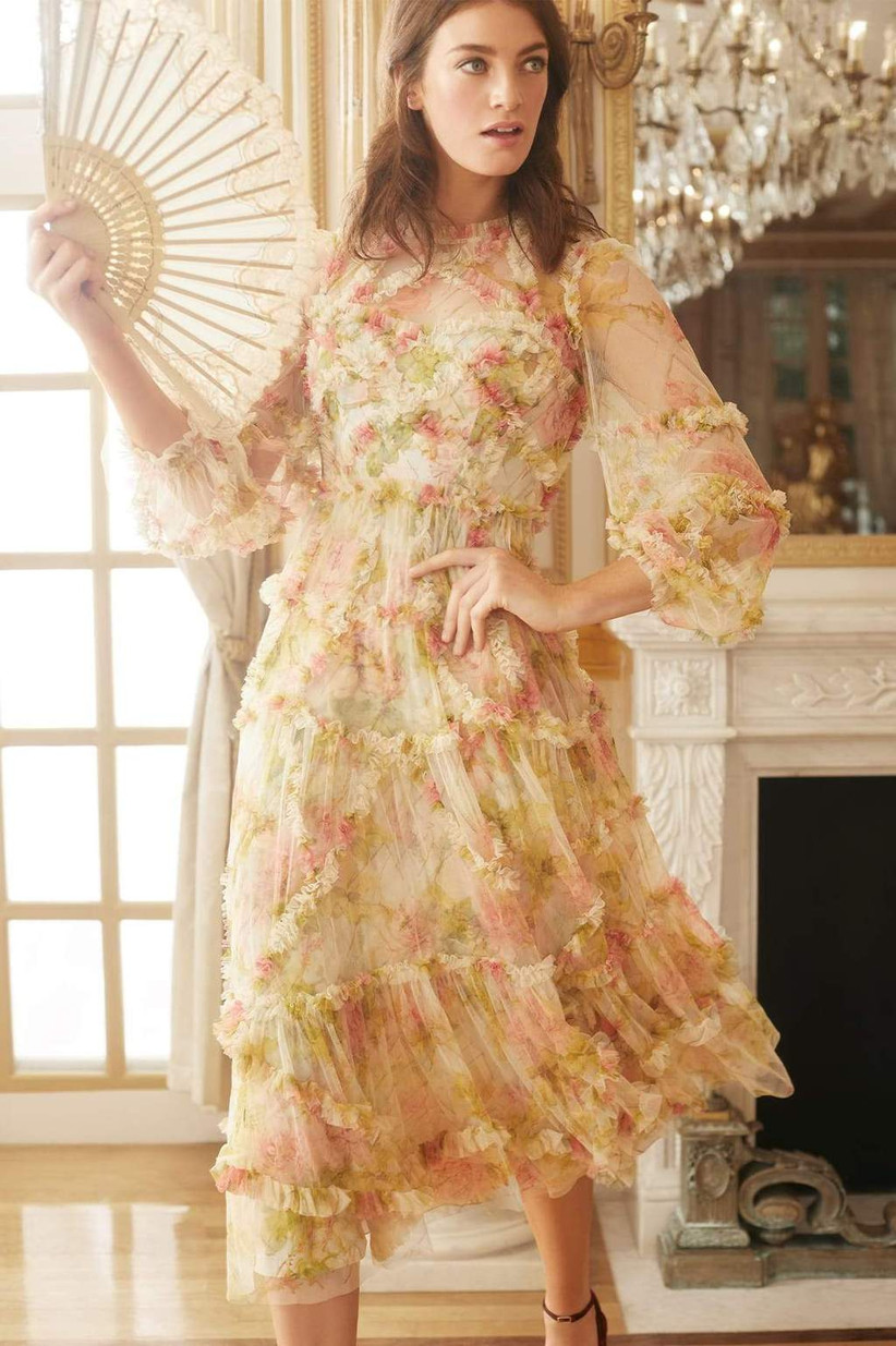 Model wearing vintage ruffled midi with pink and green florals, high neckline, and three-quarter-length sleeves