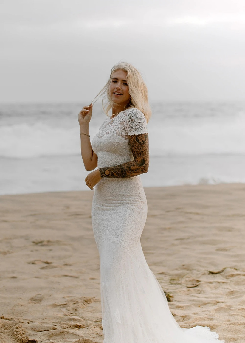 Model wearing fitted lacy wedding gown with short sleeves on the beach