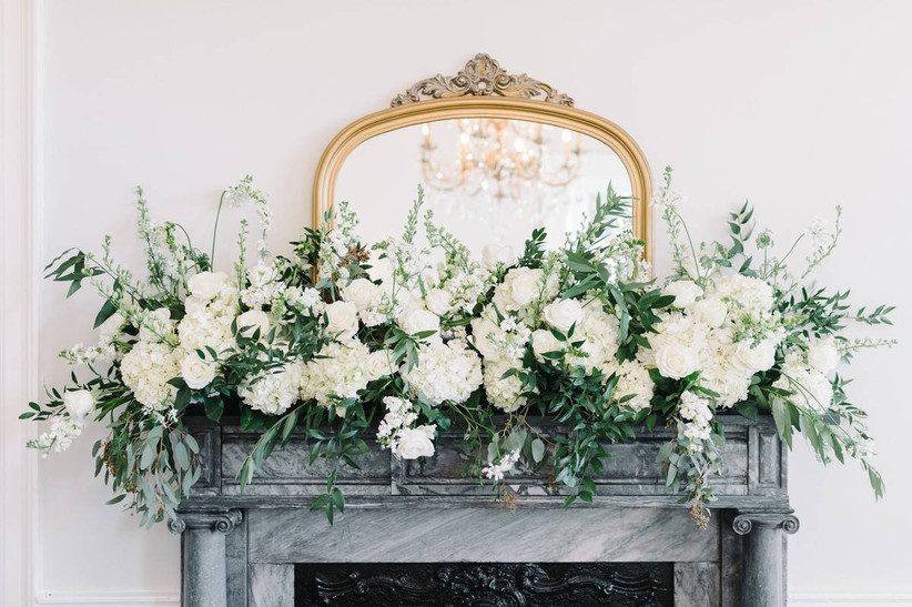 gray marble fireplace mantel is decorated with white flowers and greenery in front of antique gold frame mirror
