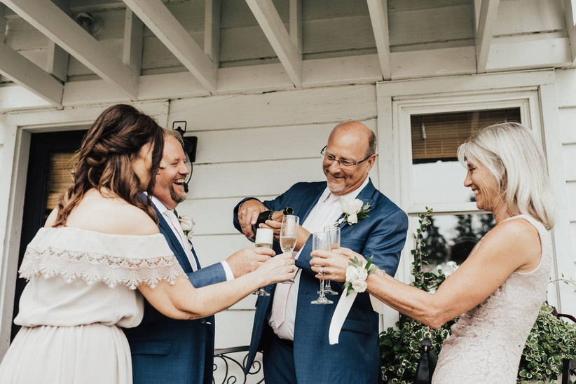 wedding couple and parents of the bride pouring champagne outdoors