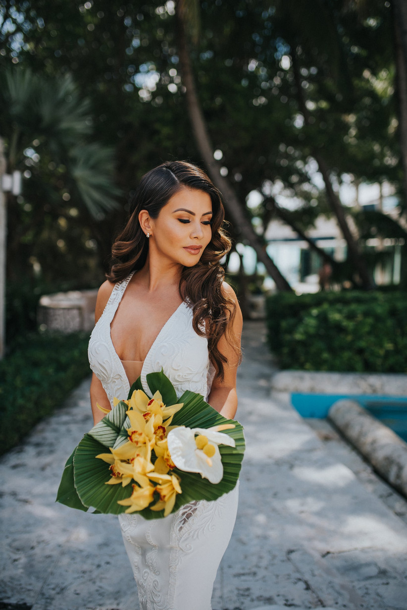 brunette bride with glam beach wedding hairstyle curls and side part