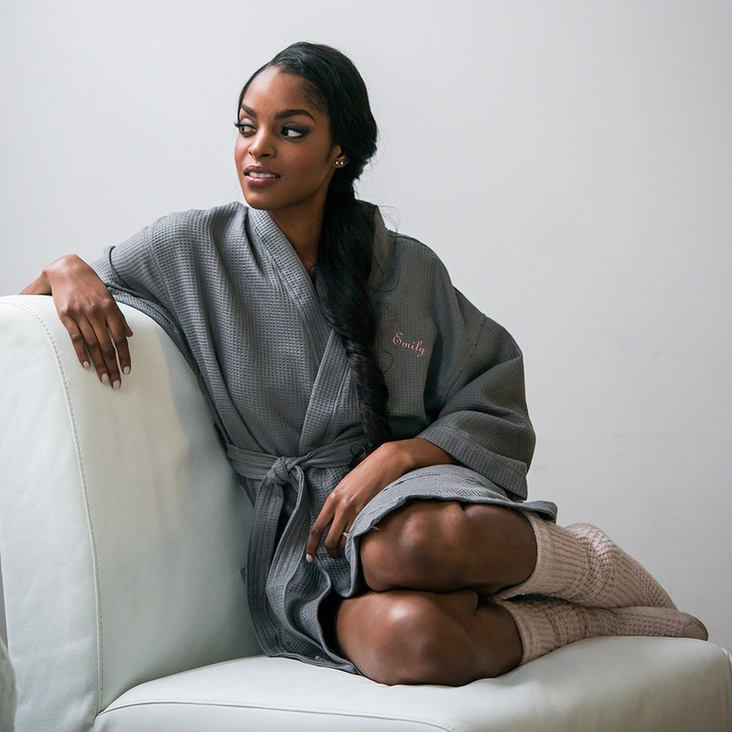 Model lounging on sofa wearing gray waffle robe embroidered with her name in pink