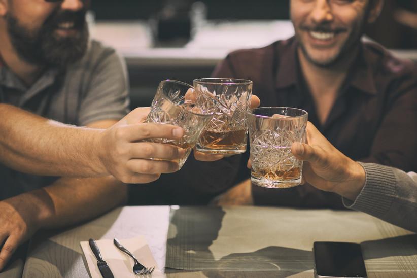 men toasting glasses of bourbon