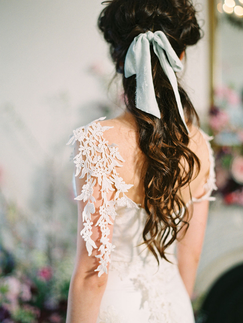 back view of brunette bride with long curly hair in a ponytail and light blue bow