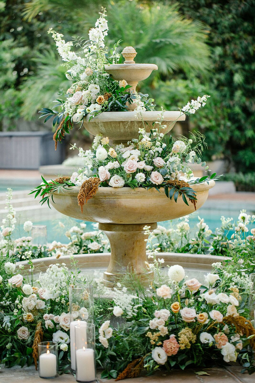 stone fountain in garden filled with flowers and greenery