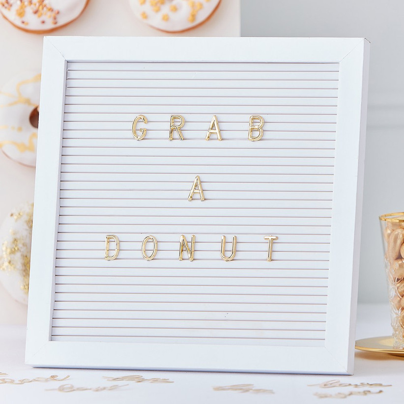 White peg letter board that reads Grab a Donut in gold letters