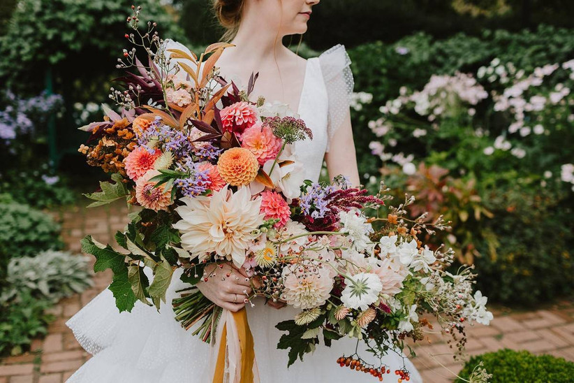 fall wedding bouquet with cafe au lait dahlias, orange pompom dahlias and abundant greenery