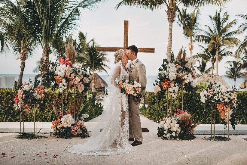 Cross wedding ceremony backdrop decorated with flowers in orange and pink tones