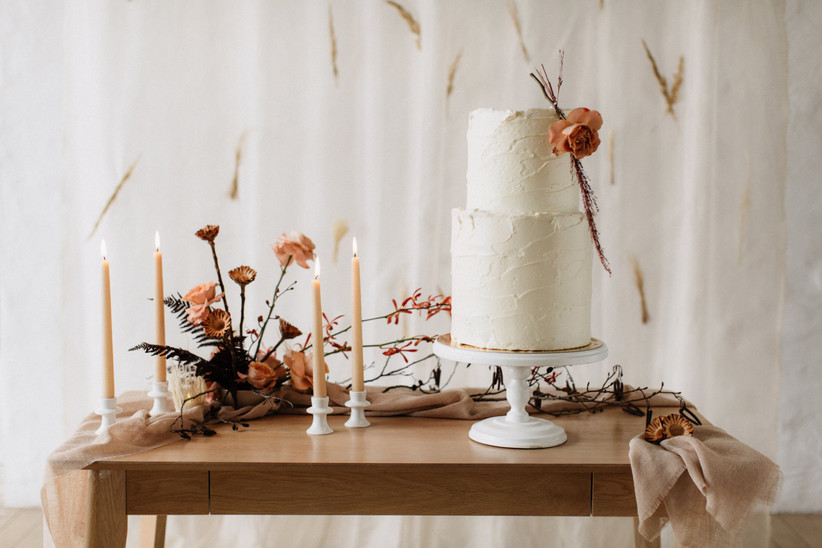 wedding cake displayed on a table surrounded by tall candles and flower arrangements