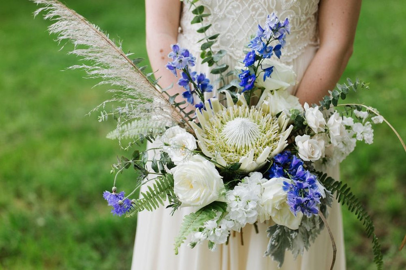 bride holding bouquet with protea, blue delphinium, white stock, pampas grass, roses, and sword ferns