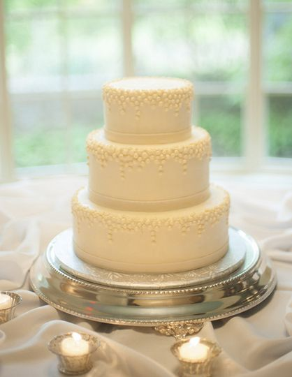 A three tier buttercream cake with cascading pearls.