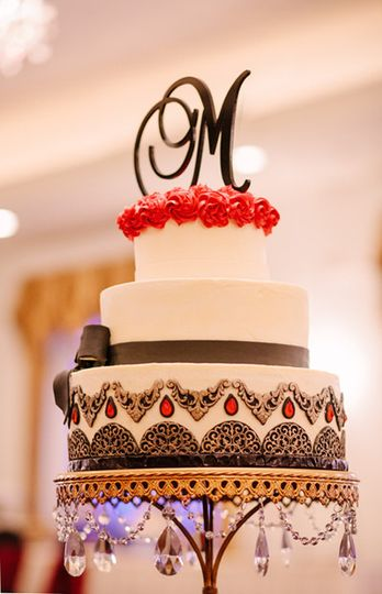 An elegant buttercream cake with edible sugar gems and gilded embellishments.