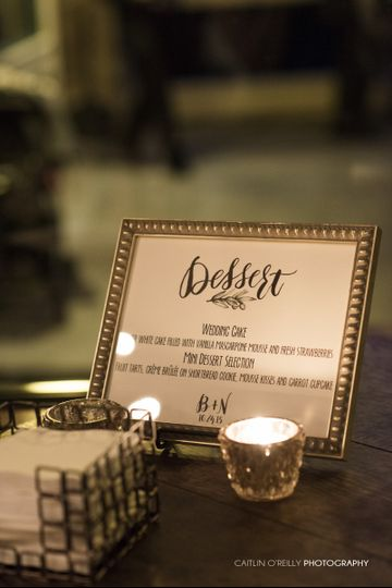 A custom dessert sign done on ecru paper with brush lettering and a sans-serif font framed in a...