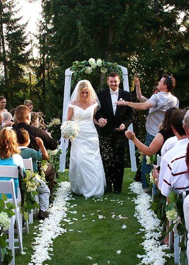 Jillian and husband walk hand in hand down petal aisle.