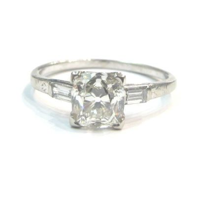 Antique cushion cut diamond engagement ring with baguette cut diamond accents, in an engraved Art...