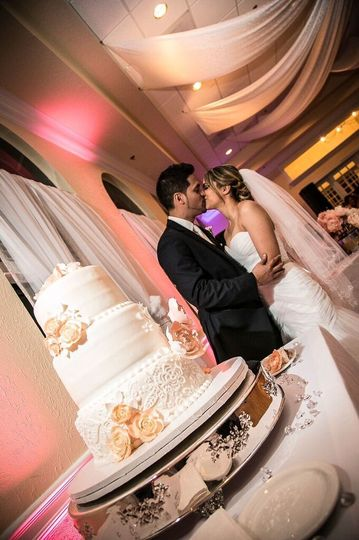Newlyweds kissing by the cake