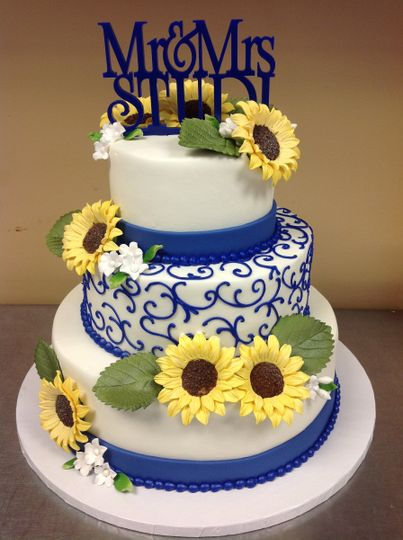 3-tier wedding cake with sunflowers and blue detailing