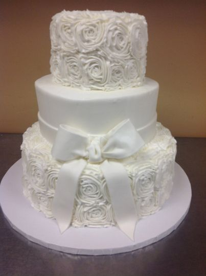 3-tier wedding cake with floral icing and white ribbon