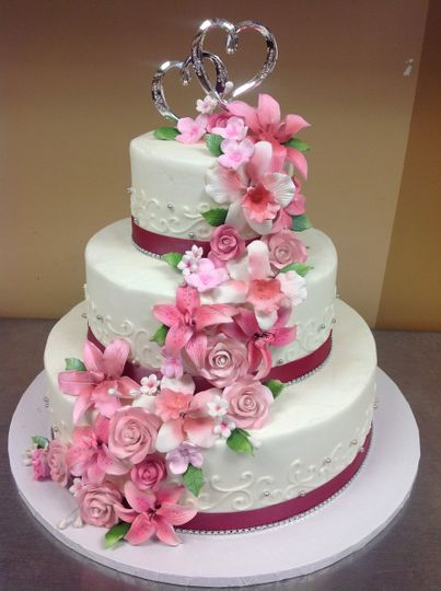 Pink flowers and lining on a 3-tier wedding cake