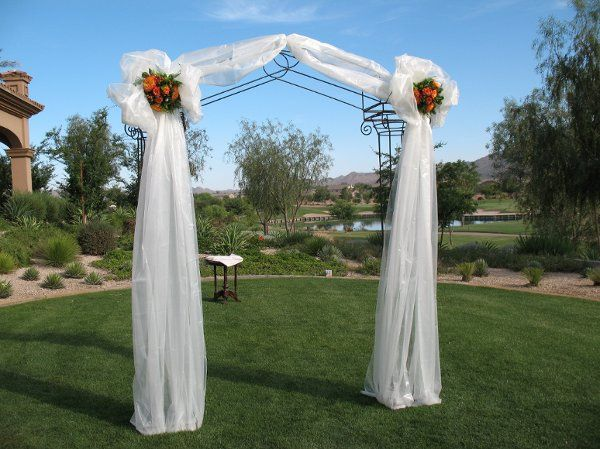 Arch decorated in white organza bows with floral center to match wedding colors.