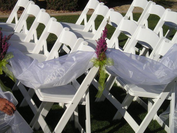 Organza aisle markers with flowers to match wedding colors.