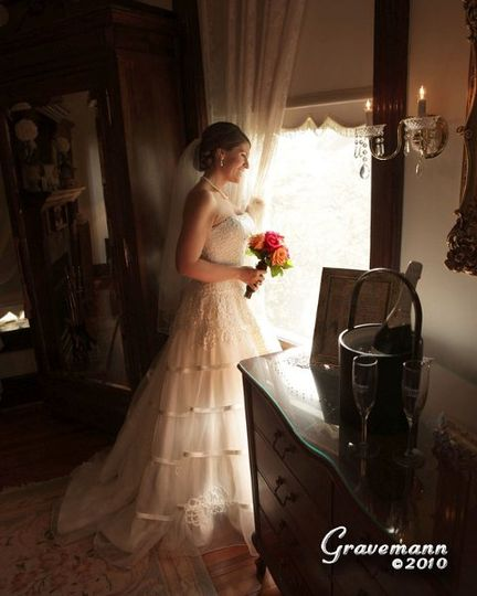 Bride on her wedding day peering out her honeymoon suite window. Experience romance 25 minutes from...