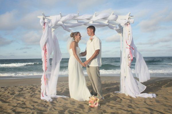 Beach wedding ceremony with white wooden arbor, decorated with white flowing fabric and ribbon.