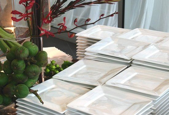 Square white hors d'oeuvres plates on the buffet