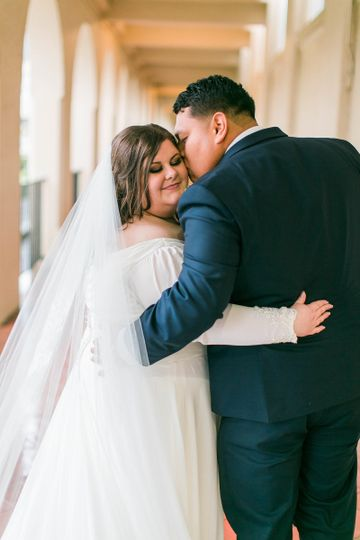 Bride embraces her groom as she gets kissed   Makeup: Hamaholic Studio. Photo: Michele Shore...
