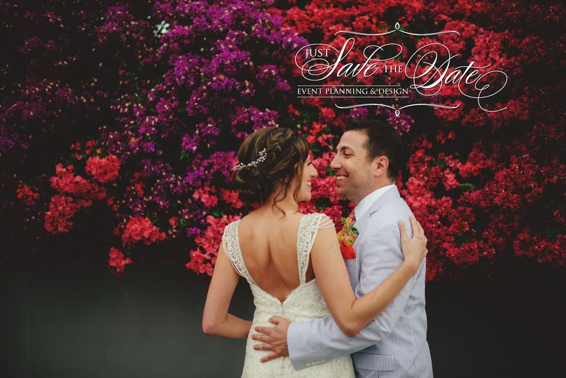 Newlyweds with flower backdrop