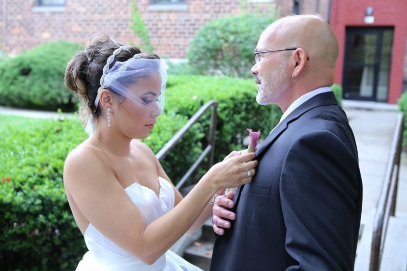 The bride pinning the boutonniere on her father.