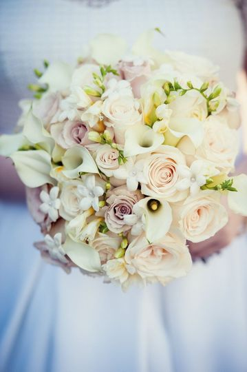 Classic bridal bouquet in ivory, cream and champagne hues featuring stephanotis, calla lily, freesia...