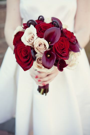 Whimsical bridesmaid bouquet with roses, calla lily and fiddle head curls.