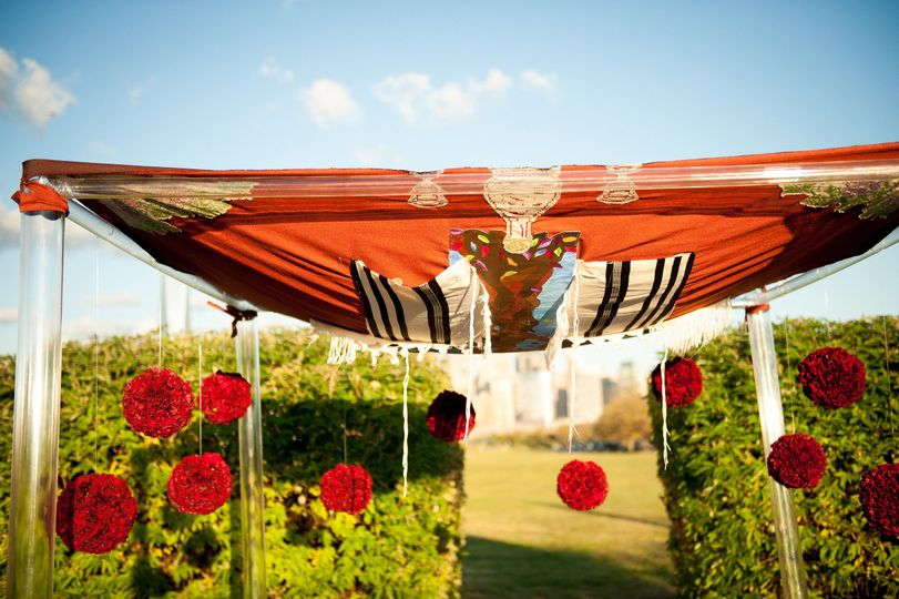 Minimalistic chuppah for an outdoor summer wedding featuring flower pomanders.
