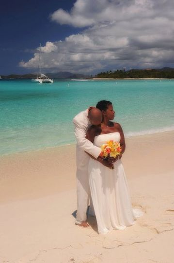 Hugging his bride at the beach