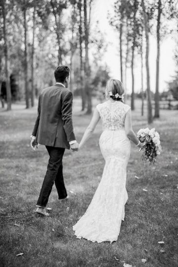 Bride and groom strolling barefoot at rice creek game farm venue photos in little falls, minnesota...