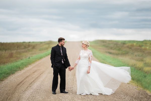 Bride and groom in the wind on a dirty road in south dakota by fargo + fergus falls wedding...