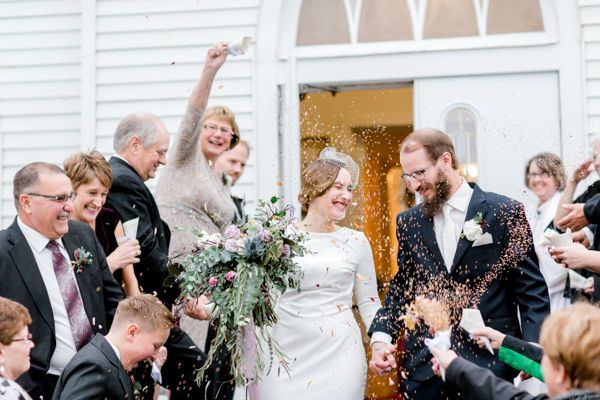 Bride and groom exiting church during flower petal toss by fargo + fergus falls wedding photographer...