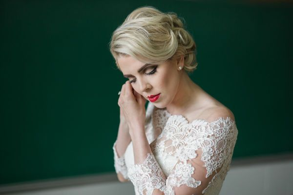 Bride putting on earrings in front of an old green chalkboard by fargo + fergus falls wedding...