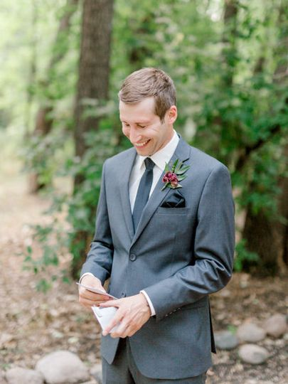 Groom opening love letter at romantic moon event center wedding venue photos by fargo + fergus falls...