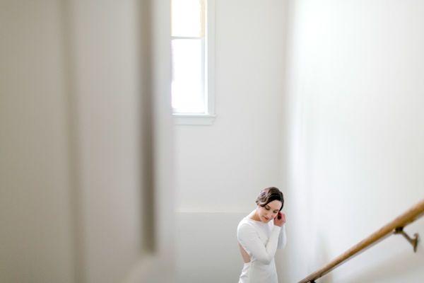 Bride putting earrings on in Halstad, Minnesota by Fargo + Fergus Falls wedding photographer Two...