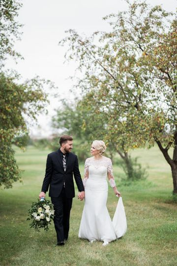 Bride and groom strolling through orchard in south dakota by fargo + fergus falls wedding...