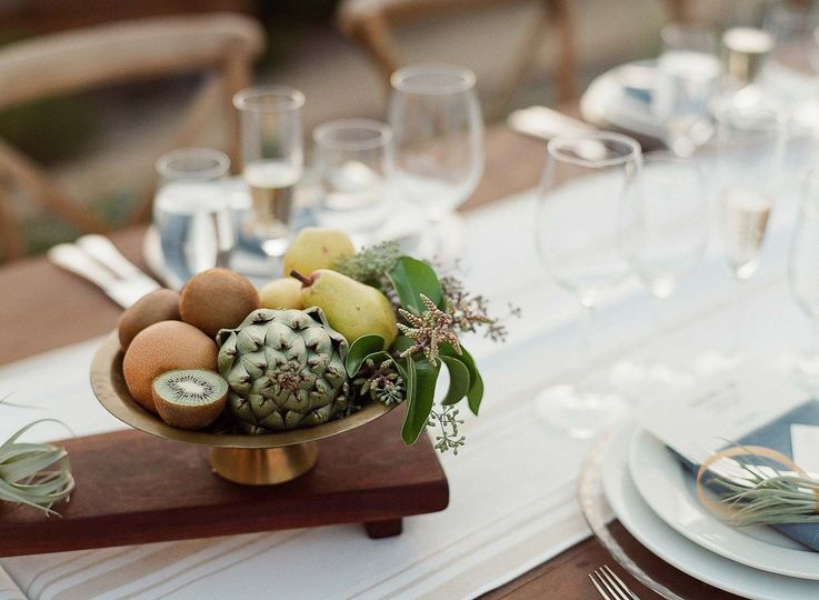 centerpiece including antique brass filled with local produce & greenery on a custom handmade walnut...