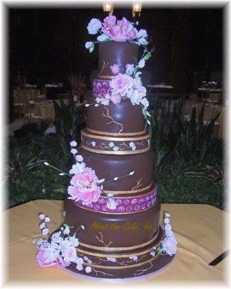 Beautiful pink sugar flowers adorn this chocolate fondant covered showpiece.  Filled with dark...